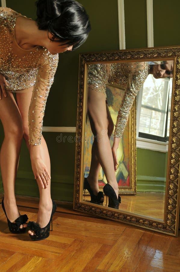 Mooie vrouw die in uitstekende toga in de spiegel kijkt stock foto's