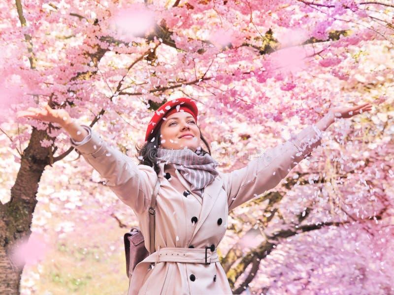Mooie vrouw die van een bloeiende de lentetuin genieten royalty-vrije stock foto