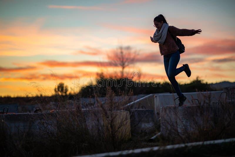 Mooie vrouw die van een concreet blok tijdens zonsondergang springen stock foto