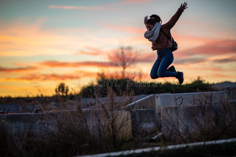 Mooie vrouw die van een concreet blok tijdens zonsondergang springen stock afbeeldingen