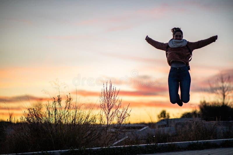Mooie vrouw die van een concreet blok tijdens zonsondergang springt stock foto