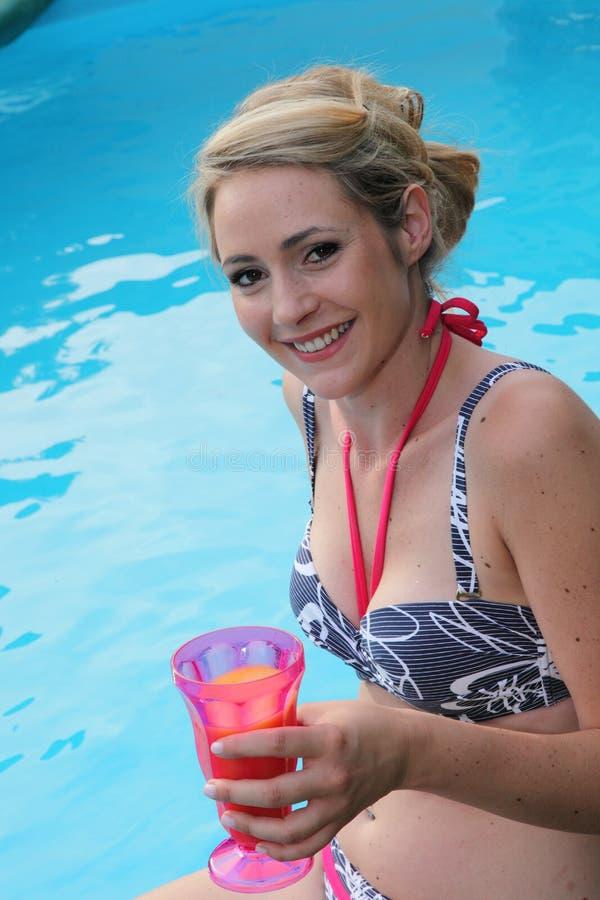 Mooie vrouw die van een drank genieten bij de pool royalty-vrije stock foto