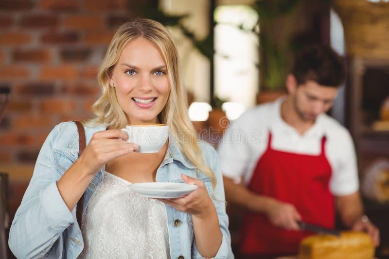 Mooie vrouw die van een kop van koffie genieten royalty-vrije stock afbeeldingen