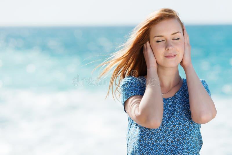 Mooie vrouw die van het zeebries genieten stock afbeelding