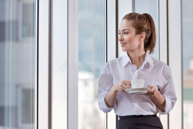 Mooie vrouw die van koffiepauze genieten op het haar werk stock foto