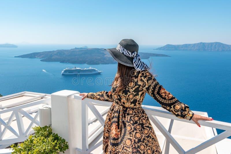 Mooie vrouw die van mening van het eiland en de Caldera van Santorini in Egeïsche overzees genieten stock foto
