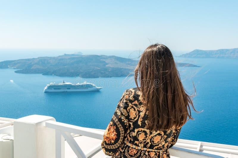 Mooie vrouw die van mening van het eiland en de Caldera van Santorini in Egeïsche overzees genieten Griekenland royalty-vrije stock foto's