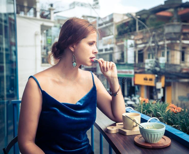 Mooie vrouw die van thee op koffieterras genieten stock afbeeldingen