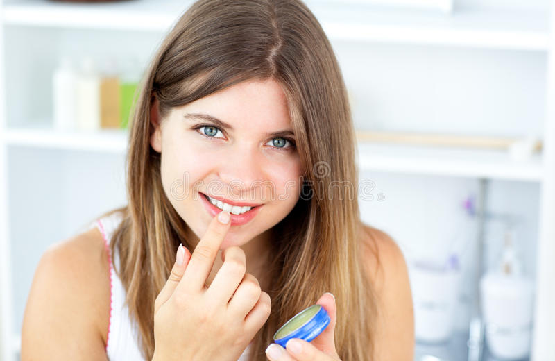 Mooie vrouw die vaseline voor haar lippen gebruikt stock afbeeldingen