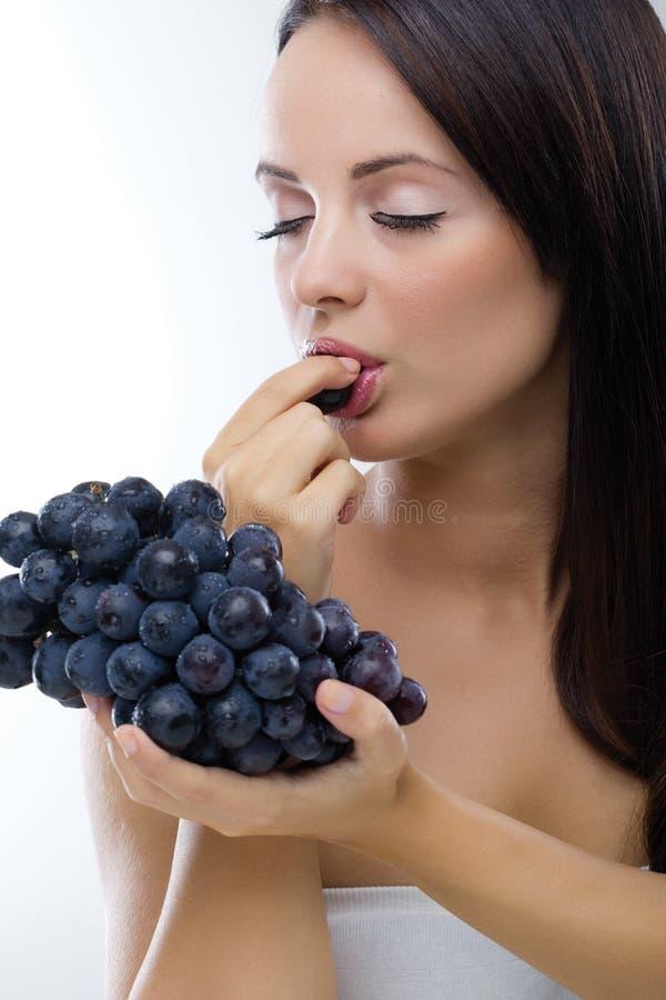 Mooie vrouw die verse druiven eten royalty-vrije stock afbeelding