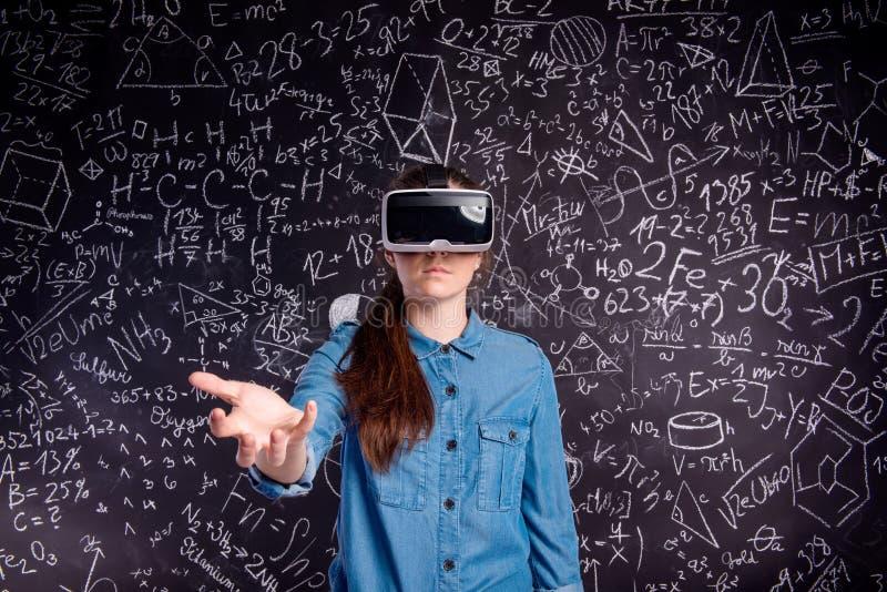 Mooie vrouw die virtuele werkelijkheidsbeschermende brillen dragen tegen grote blac royalty-vrije stock afbeelding