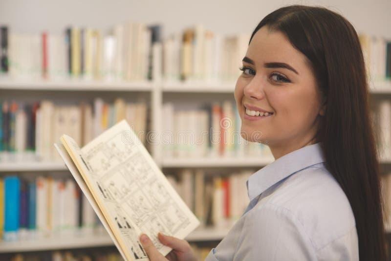 Mooie vrouw die voor boeken bij de opslag winkelen royalty-vrije stock afbeelding