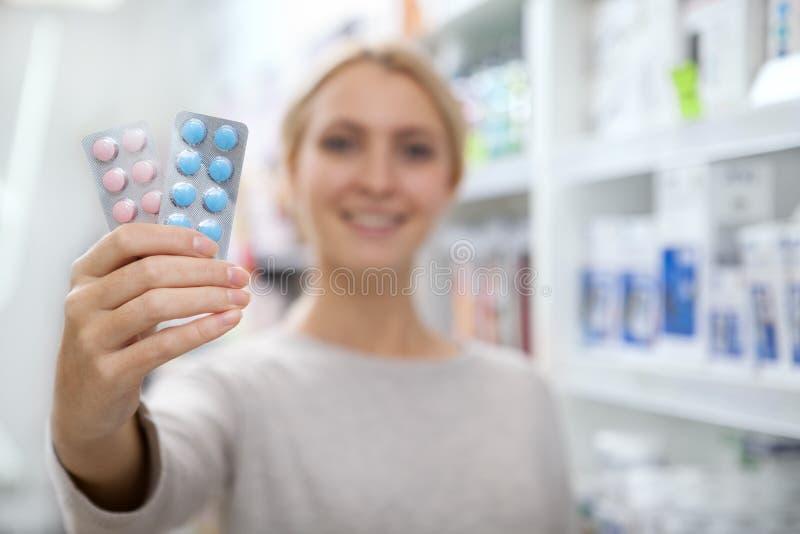 Mooie vrouw die voor geneeskunde winkelen stock afbeelding