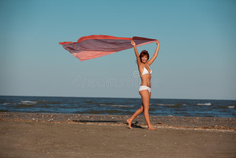 Mooie vrouw die voor het strand van de vreugdewoestijn springt royalty-vrije stock afbeelding