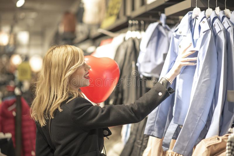 Mooie vrouw die voor kleren winkelen stock fotografie