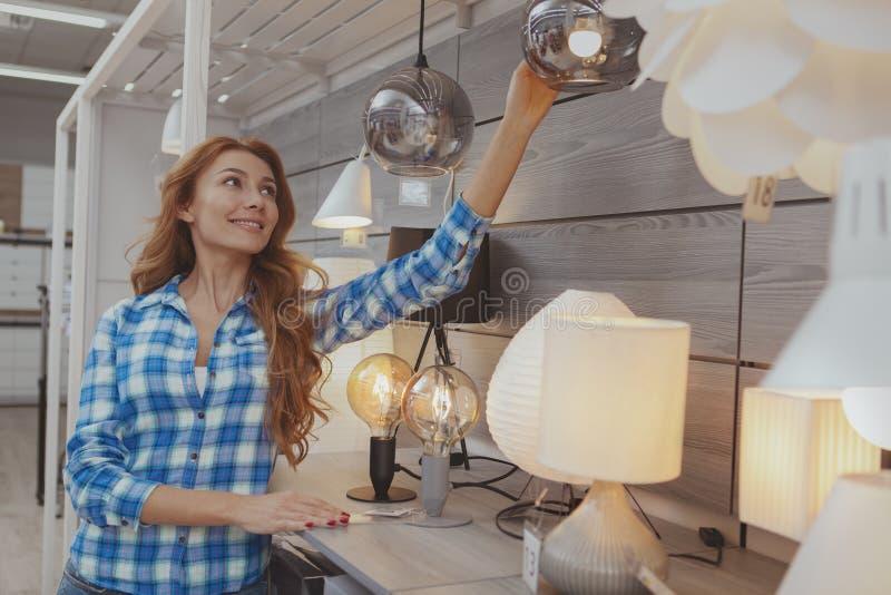 Mooie vrouw die voor milieuvriendelijke verlichting winkelt stock foto