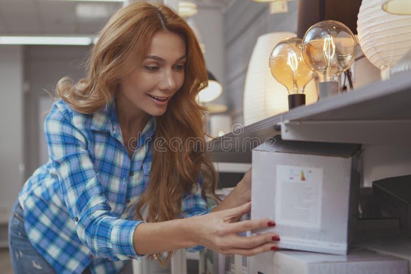 Mooie vrouw die voor milieuvriendelijke verlichting winkelt stock fotografie