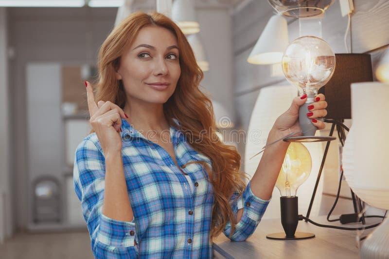 Mooie vrouw die voor milieuvriendelijke verlichting winkelt stock foto's