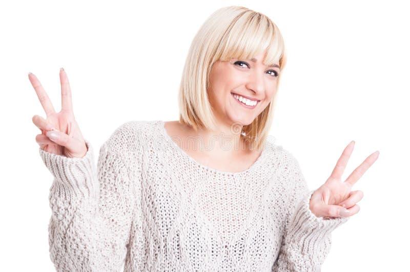 Mooie vrouw die warme sweter dragen die dubbele vrede tonen stock afbeeldingen