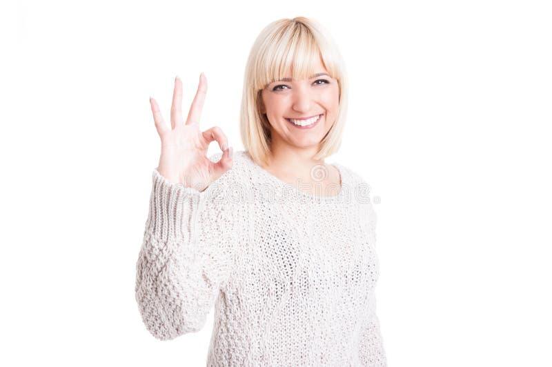 Mooie vrouw die warme sweter dragen die o.k. gebaar tonen royalty-vrije stock foto