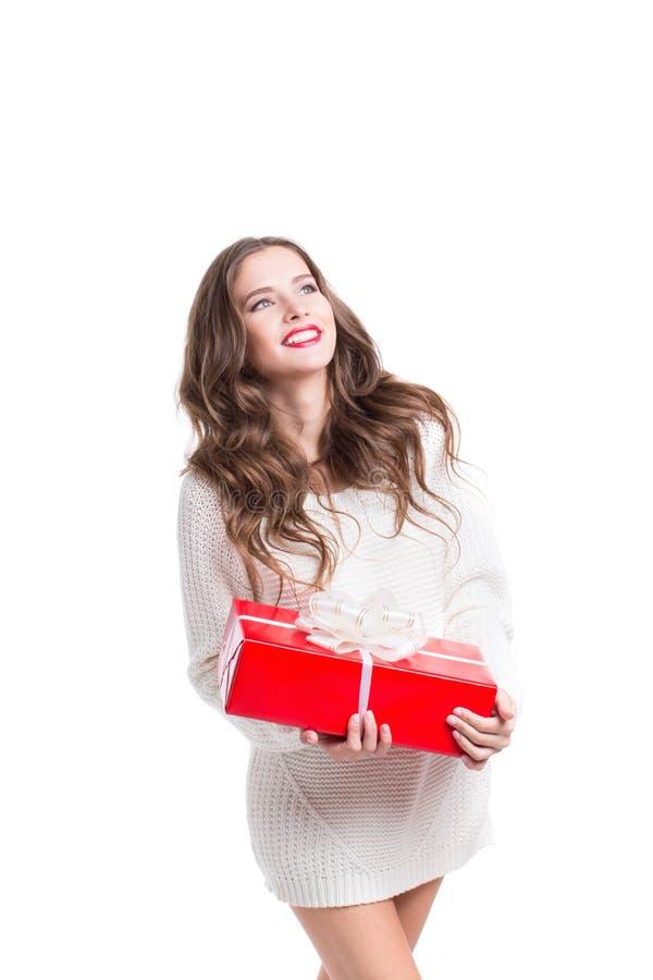 Mooie vrouw die in witte sweater een rode doos met een gift en het glimlachen houdt stock fotografie