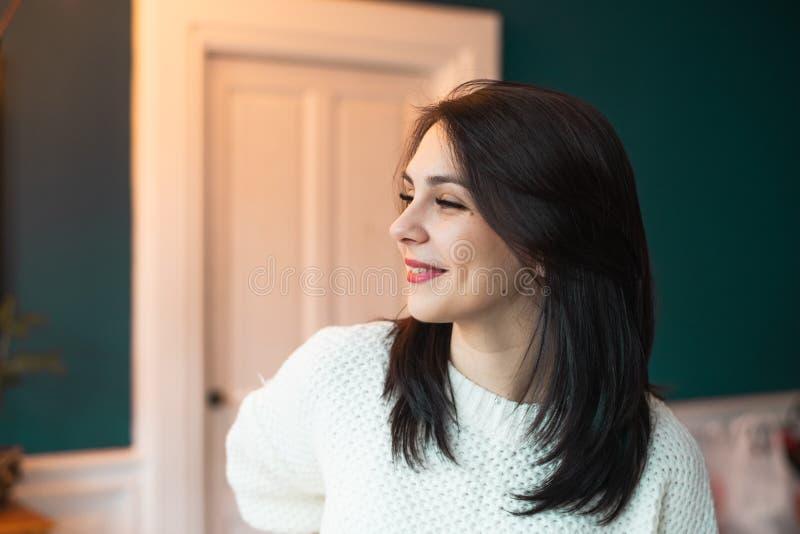 Mooie vrouw die in witte sweater glimlachen, die weg eruit zien royalty-vrije stock afbeeldingen