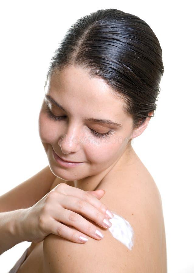 Mooie vrouw die witte vochtinbrengende crème zet royalty-vrije stock afbeelding