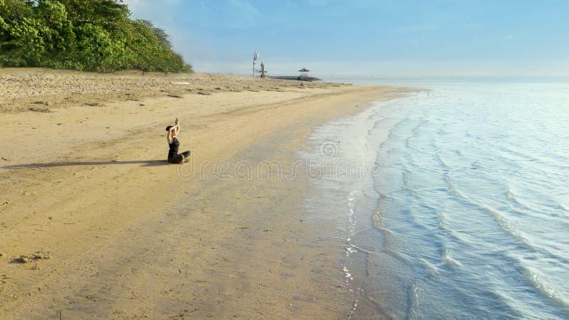 Mooie vrouw die yoga op het Sanur-strand uitoefenen royalty-vrije stock afbeelding