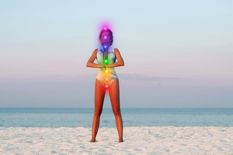 Mooie vrouw die yoga op het strand doen stock foto