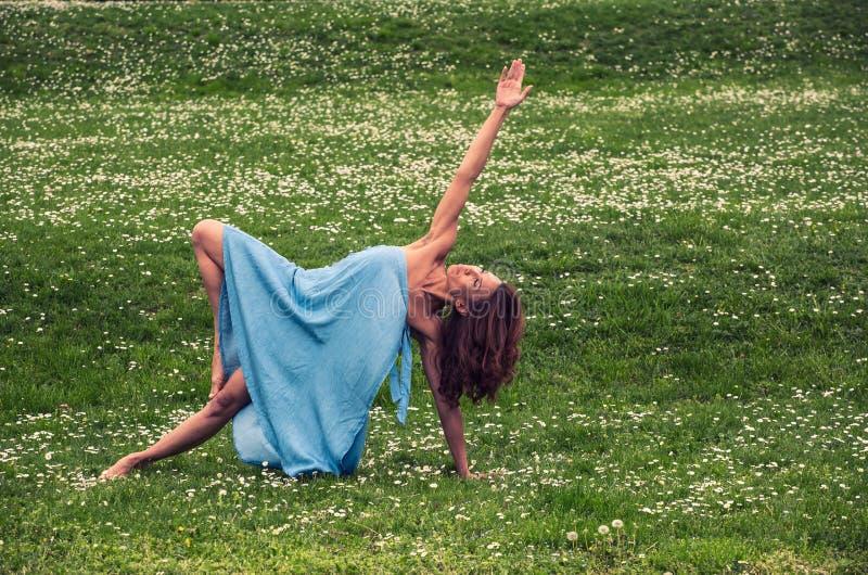 Mooie vrouw die yoga op weide doen royalty-vrije stock fotografie