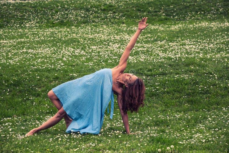Mooie vrouw die yoga op weide doen royalty-vrije stock foto's