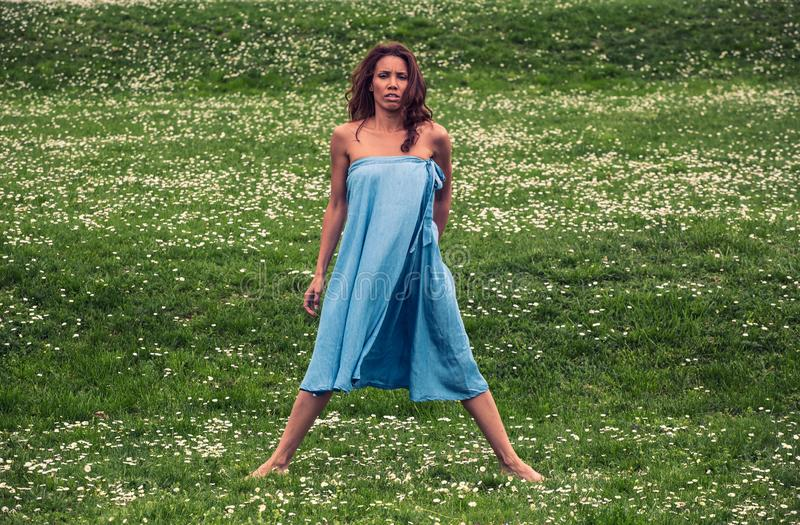 Mooie vrouw die yoga op weide doen stock fotografie