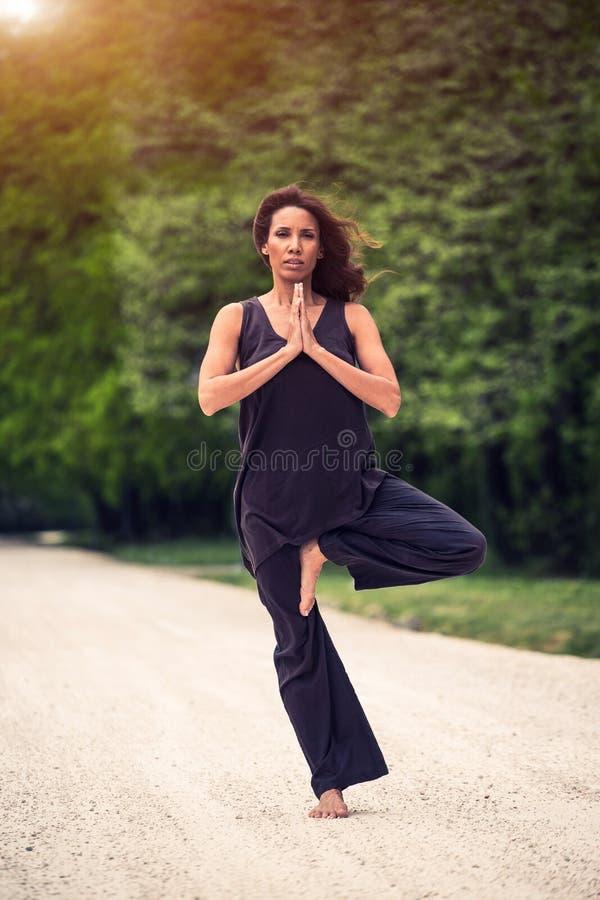 Mooie vrouw die yoga op weide doen royalty-vrije stock afbeeldingen