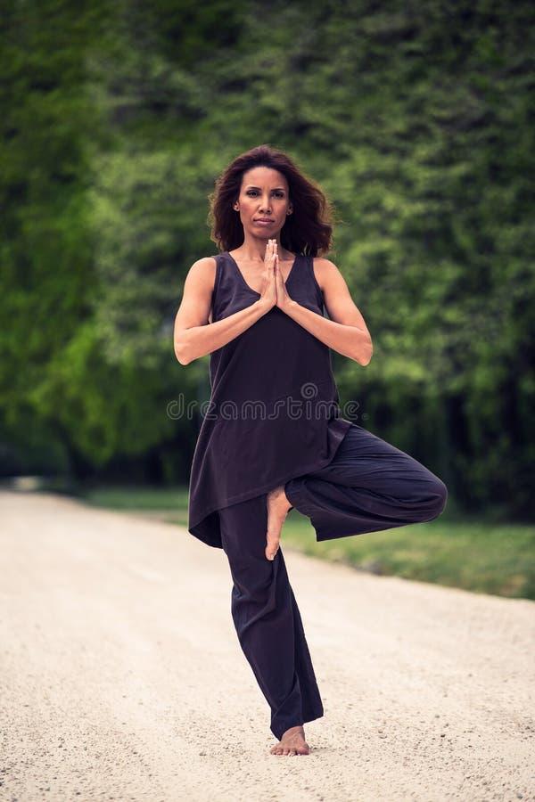 Mooie vrouw die yoga op weide doen royalty-vrije stock afbeelding
