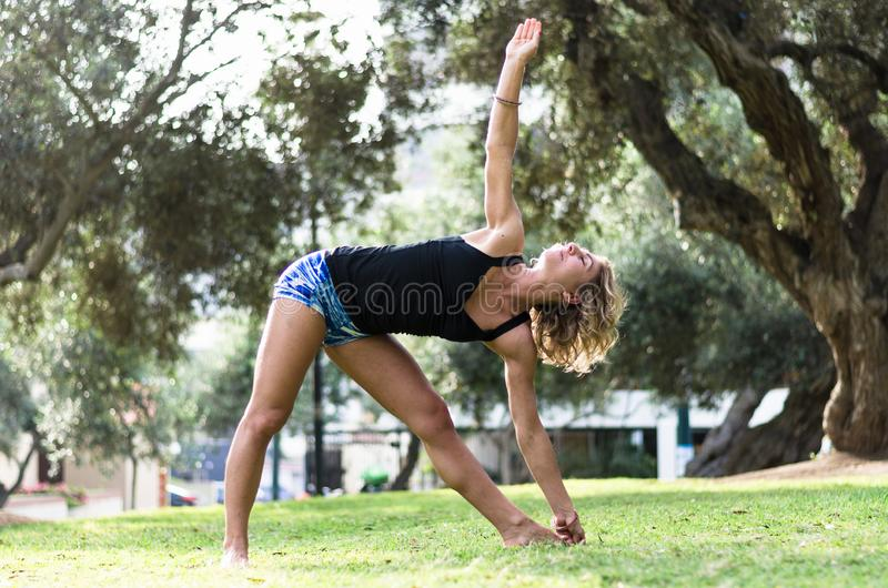 Mooie vrouw die yoga in openlucht in het park doen stock foto