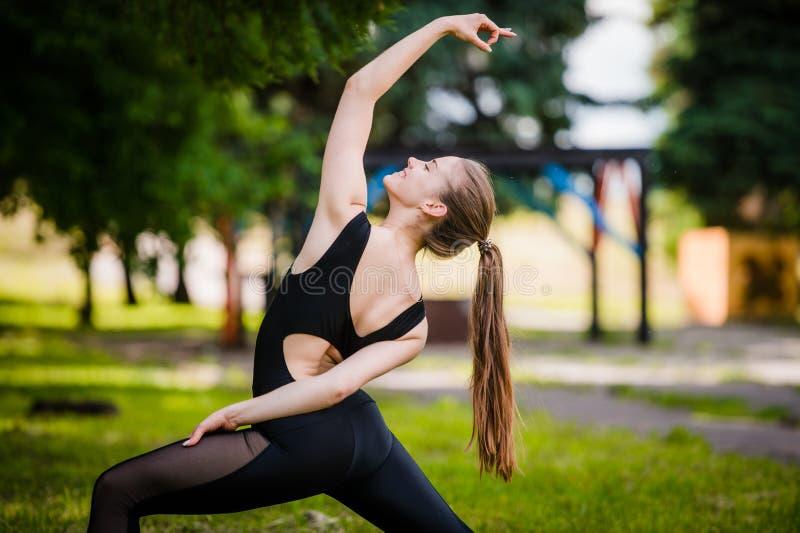Mooie vrouw die yogaoefeningen in het park doen stock foto's