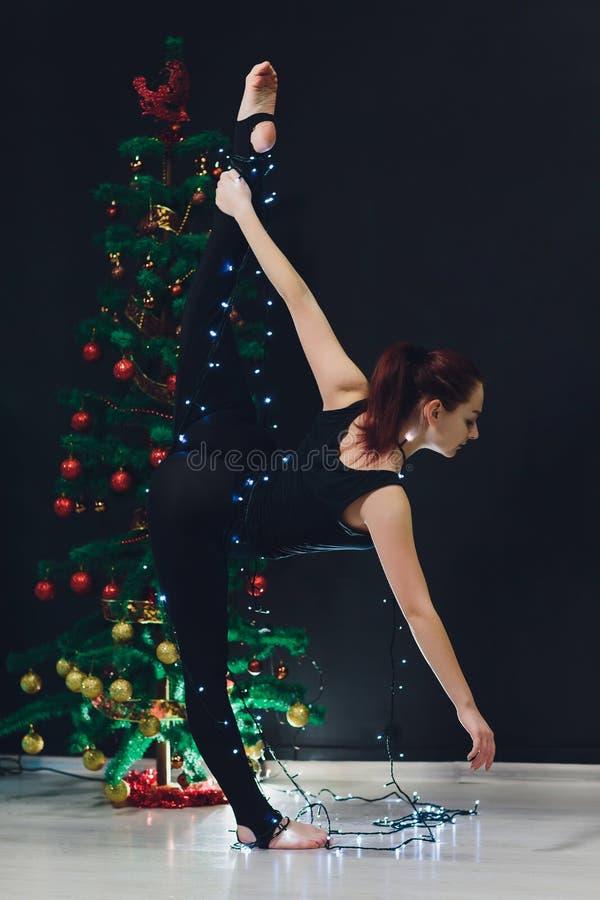 Mooie vrouw die yogaturner op de Kerstmisachtergrond doen stock afbeeldingen