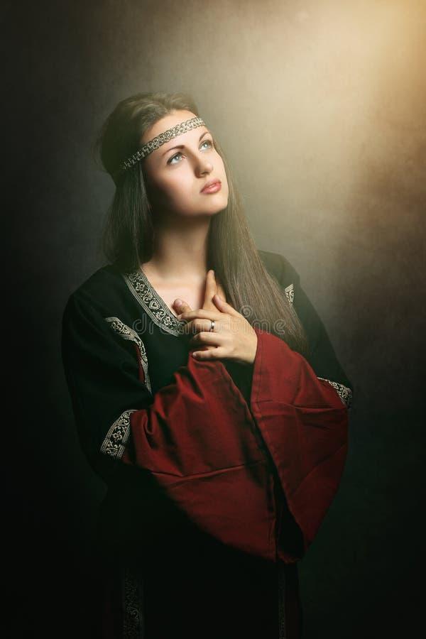 Mooie vrouw die in zacht heilig licht bidden stock foto's