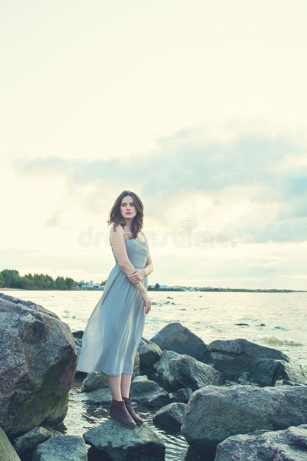 Mooie vrouw die zich alleen op oceaankust, eenzaamheids en depressieconcept bevinden stock afbeelding