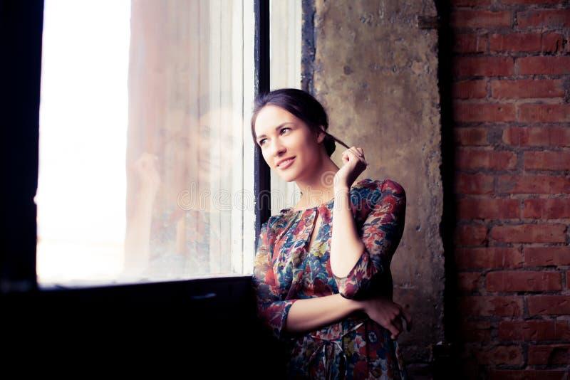 Mooie vrouw die zich door venster te kijken bevinden royalty-vrije stock afbeelding