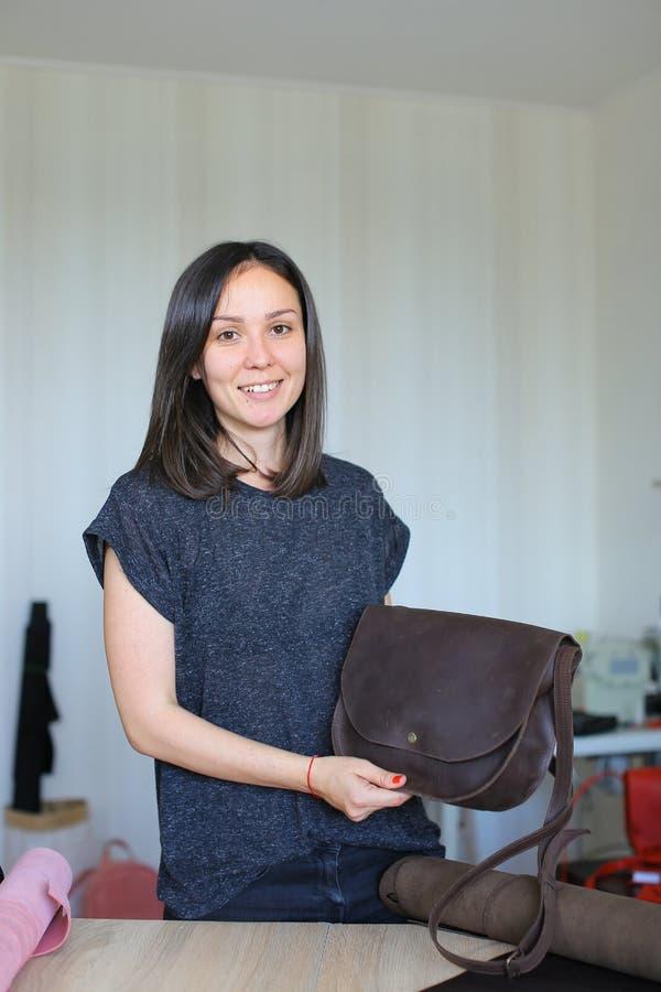 Mooie vrouw die zich met bruine leer met de hand gemaakte zak bij atelier bevinden royalty-vrije stock afbeeldingen