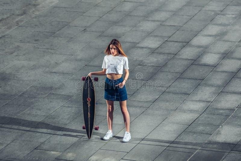 Mooie vrouw die zich met longboard in de stad bevinden royalty-vrije stock afbeeldingen