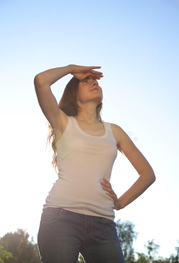 Mooie vrouw die zich tegen de hemel bevinden Zonnige dag royalty-vrije stock foto's