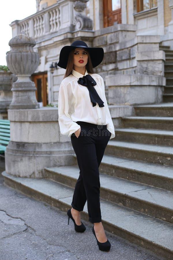 Mooie vrouw die zoals een dame past elegante kleren dragen, die bij park stellen stock afbeeldingen