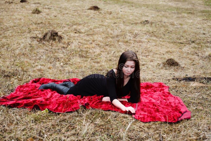 Mooie vrouw die in zwarte kleding op rode stof leggen Hay Background stock foto's