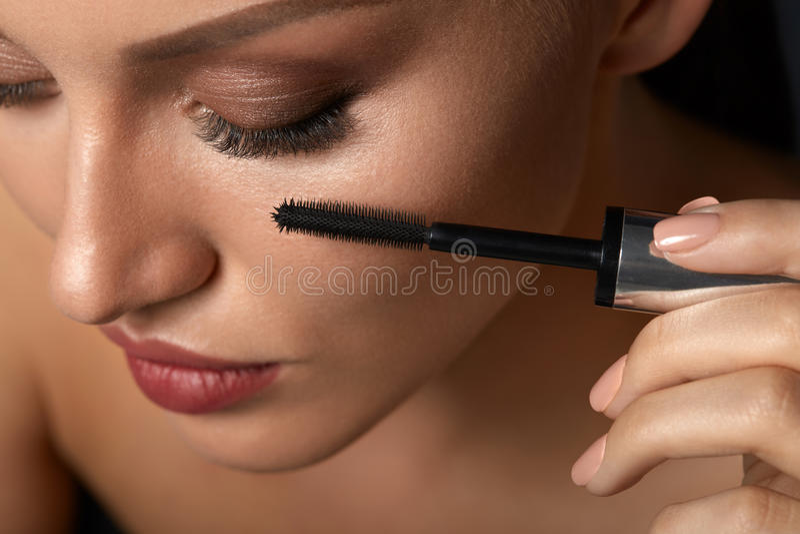 Mooie Vrouw die Zwarte Mascara op Gesloten Ogen gebruiken stock foto