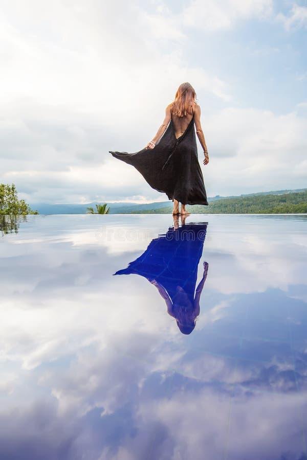 Mooie vrouw door de pool stock afbeelding