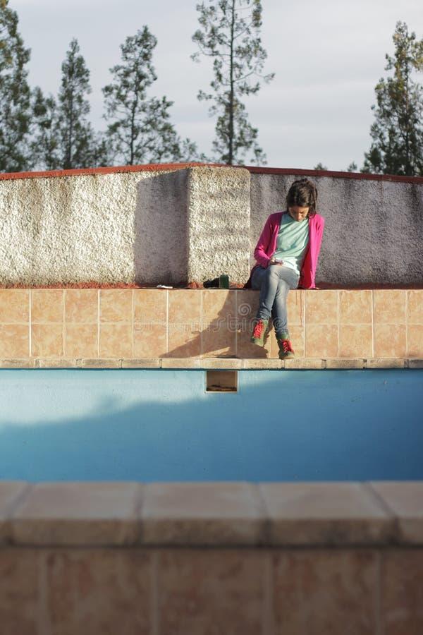 Mooie vrouw door de pool met smartphone royalty-vrije stock foto's