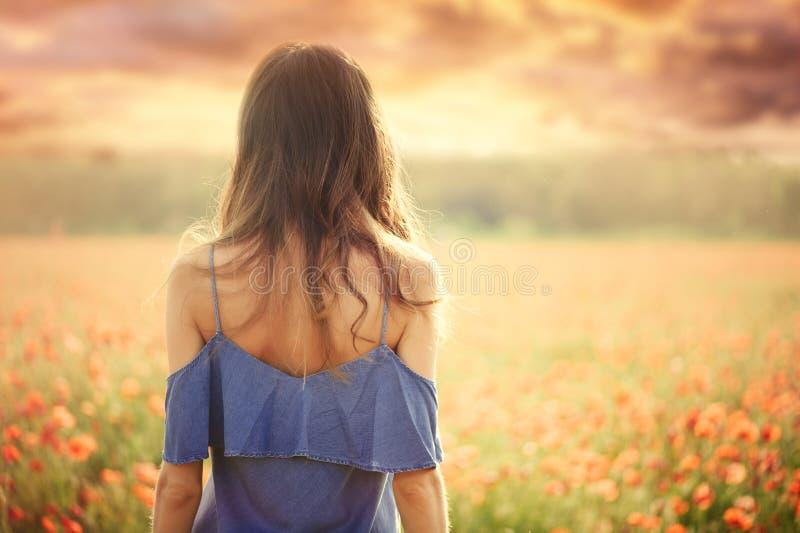 Mooie vrouw in een blauwe kleding op een tarwegebied bij zonsondergang van het achter, warme stemmen, geluk en een gezonde levens stock foto