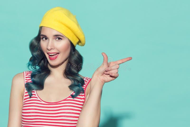 Mooie vrouw in een gele baret die vinger op copyspace richten stock afbeeldingen